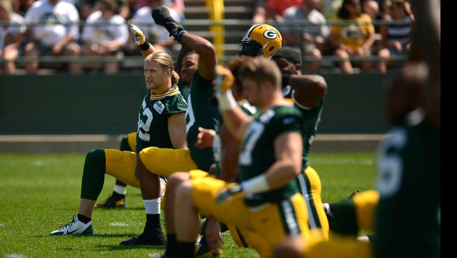 Green Bay Packers linebacker Clay Matthews stretches with his teammates during training camp practice at Ray Nitschke Field on Saturday, Aug. 15, 2015.