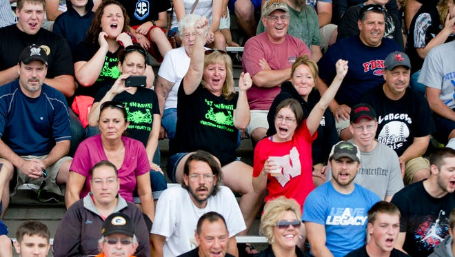 The audience cheers for the demolition derby drivers at the Manitowoc County Fair grandstand on Sunday, Aug. 30. The crowd filled the main grandstand to watch the demo derby races.
