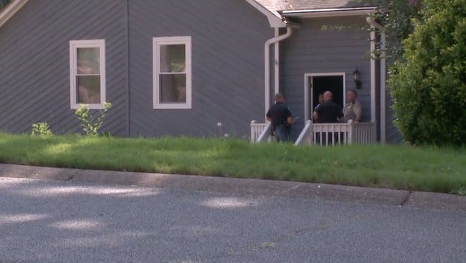 Officers stand outside the home in Marietta, Ga.