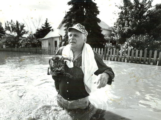Larry Katz carries a very distraught looking Tom the cat Sunday, July 11, 1993. Katz rescued Tom from a home in Valley Junction.
