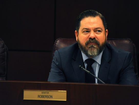 Senator Michael Roberson listens to a speaker during