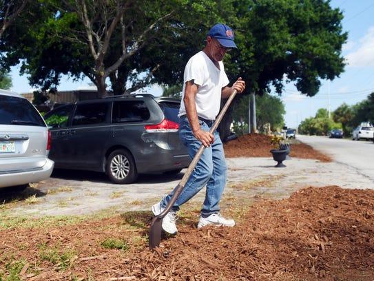 Robert Adamski helps spread mulch around the grounds