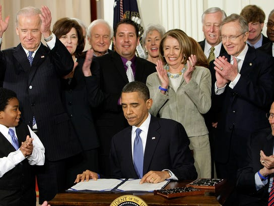 FILE - In this March 23, 2010, file photo, participants applaud in the East Room of the White House in Washington, Tuesday, March 23, 2010, as President Barack Obama, flanked by Macelas Owens of Seattle, left, and Rep. John Dingell, D-Mich., right, signs the health care bill.