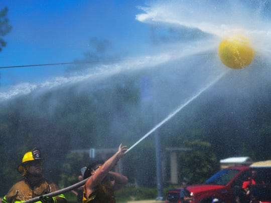 In Waterball, teams of firefighters compete by using firehoses to push a ball suspended from a wire.