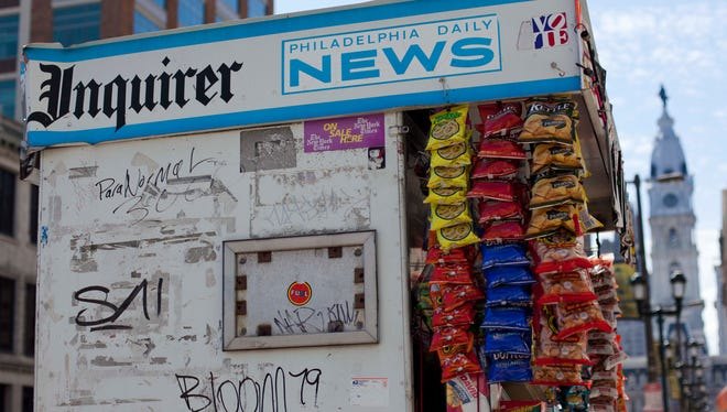 A newsstand displays the logos of The Philadelphia Inquirer and Daily News in view of City Hall in Philadelphia.