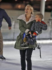 Lindsey Opp, of Clive, skated holding her son, Maverick, at the Brenton Skating Plaza for the outdoor ice skating rink's opening for the 2013-2014 season on Thursday Nov. 14, 2013.