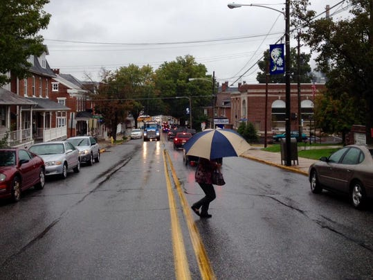 A pedestrian dodges rain and traffic while crossing South Main in downtown Spring Grove on Thursday.