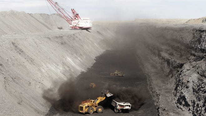 A front end loader dumps coal into a hauler on Oct. 9, 2013, in a section of the Navajo Mine in Fruitland.