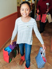 Lillyanna Martinez, 10, carries various gifts to a