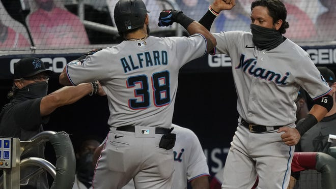 Miami Marlins' Jorge Alfaro, left, celebrates with Miguel Rojas, right, after Alfaro hits a home run during the third inning of the team's baseball game against the Atlanta Braves on Tuesday, Sept. 8, 2020, in Atlanta.