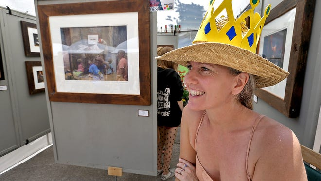 """Temporary """"Queen"""" Victoria Hemminghaus sits at her husband Matthew's photography booth at the Des Moines Arts Festival. She's wearing a crown that was passed around among the artists in a game sort of like tag."""