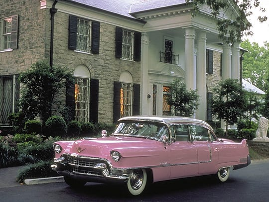 A vintage pink Cadillac parked in front of Graceland, Elvis Presley's Memphis home, which is a local institution and popular tourist draw.