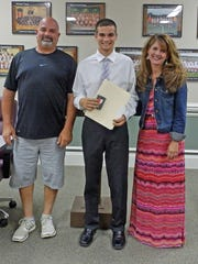 Robert Erianne (center) with his parents, Robert and