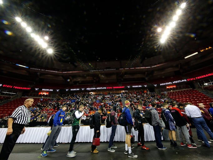 Division 1 wrestlers wait to weigh in before the start
