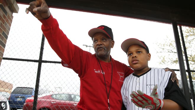 West End Reds CEO Fred Carnes points to where Candon Wilborn, 9, should position himself at Weaver Field. About 100 children participate in the baseball program.