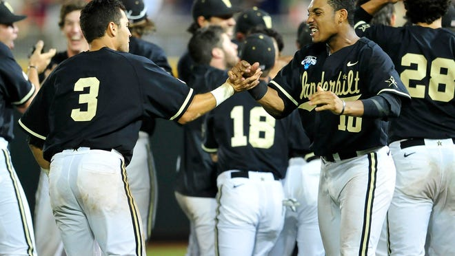 Vanderbilt players including John Norwood (10) and Vince Conde (3) celebrate a 4-3 win over Texas at the College World Series at TD Ameritrade Park in Omaha, Neb., Saturday, June 21, 2014.