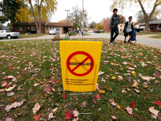 Students walk past a sign protesting sidewalks in Windsor