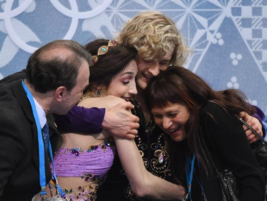 Meryl Davis and Charlie White receive hugs in the kiss and cry area, including from coach Marina Zoueva (right) after receiving their scores during the ice dance free dance program during the Sochi 2014 Olympic Winter Games at Iceberg Skating Palace. Zoueva is moving her International Skating Academy from Michigan to Hertz Arena in Estero in February.