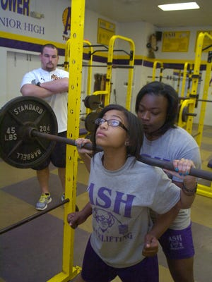 Alexandria Senior High powerlifters Ashley Mitchell (center) and Tamera Lusk (right) practice as their coach Brad Chesshir looks on inside the Trojans weight room.