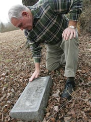 Former SPCA Director John Caldwell kneels beside a head stone in the pet cemetery in a 2007 photo.