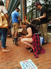 The merchants of downtown Red Bank hosted the 62nd Annual Red Bank Sidewalk Sales July 29,30,31, 2016. Menley Taylor (kneeling) pets Penelope, a three year old Pomeranian, at Urban Outfitters on Broad Street.
