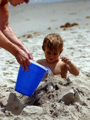 Sherry Wian buries her grandson Tanner Hagan, 5, in the sand while enjoying a day at the beach during the last weekend of Brevard County's spring break at Indialantic beach in 2008.