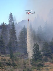 A Nevada Division of Forestry helicopter makes water drops on the Garson Fire Sunday afternoon.  The fire that started Sunday afternoon was 10% contained and had burned 125 acres as of 5:00 p.m. near Verdi, Nevada.