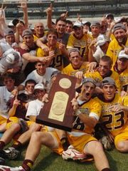 Salisbury University's Kyle Hartzell holds the trophy as the rest of the team celebrates after winning the NCAA Men's Division III Lacrosse title in 2007.