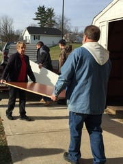 Betty Scudder helps carry donated desks into New Haven