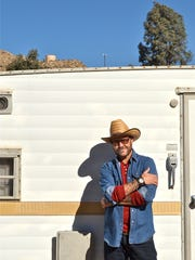 Clay Cross poses in front of the vintage trailer that serves as a casita at the Morongo Valley home he shares with his life partner. They bought their home about three years ago, fixed it up, and Cross began the challenging process of finding full-time work. He starts a new job in December that values his professional experience and fully accepts his gender identity as a transgender man.