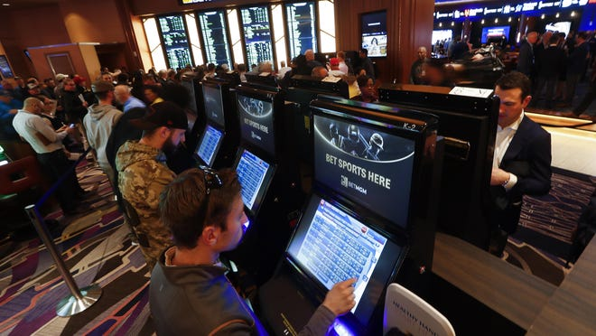 In this March 11, 2020, file photo, patrons place in person bets during the launch of legalized sports betting in Michigan at the MGM Grand Detroit casino in Detroit. Michigan casinos could launch online sports betting and gambling games in December once state lawmakers waive the remaining time they have to review proposed licensing rules.