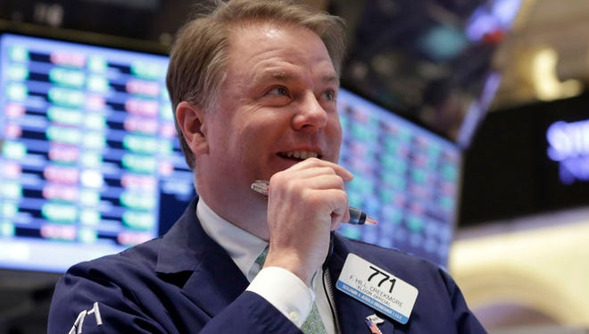 A trader at the New York Stock Exchange smiles during February trading on the Big Board.