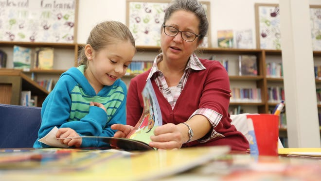Longtime volunteer Mary Kuenzi reads with second-grader Madison Allies as part of the SMART (Start Making A Reader Today) program Thursday, Nov. 5, 2015, at Englewood Elementary School in Salem. SMART is seeking volunteers for the 2016-17 school year.