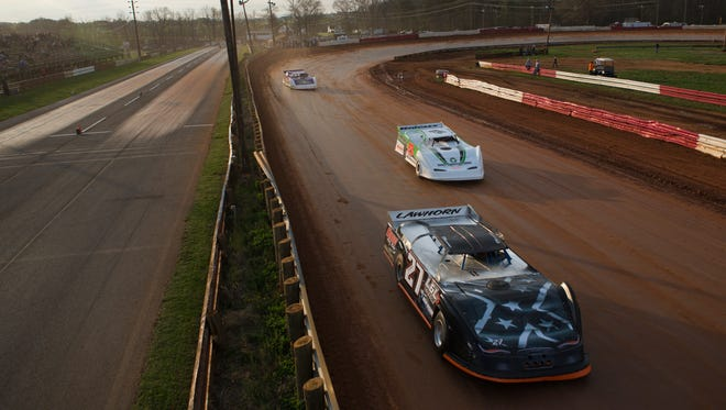 Late model cars roar around the new dirt track at Eastside Speedway on opening night for stock cars Saturday, April 18, 2015.