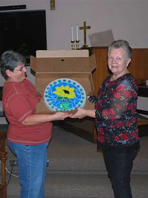 Baxter County Master Gardener Sue Chamberlin presents outgoing president Phyllis Henley with a gift from the membership at the group'srecent Holiday Luncheon. Henley served two terms as President of the Master Gardeners.