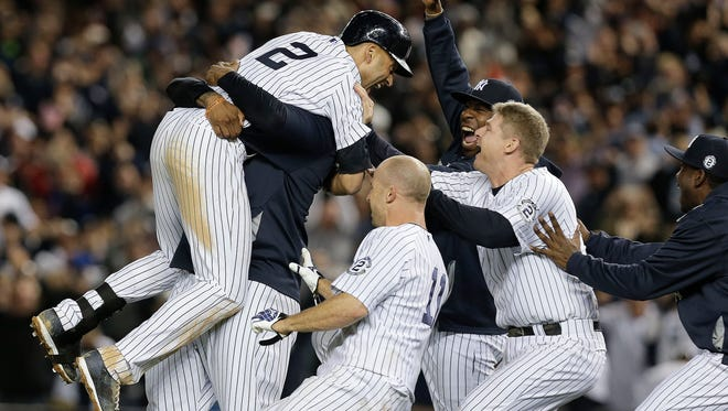 New York Yankees' Derek Jeter (2) is mobbed by teammates after driving in the winning run with a single against the Baltimore Orioles in the ninth inning of a baseball game, Thursday, Sept. 25, 2014, in New York. The Yankees won 6-5. (AP Photo/Julie Jacobson)