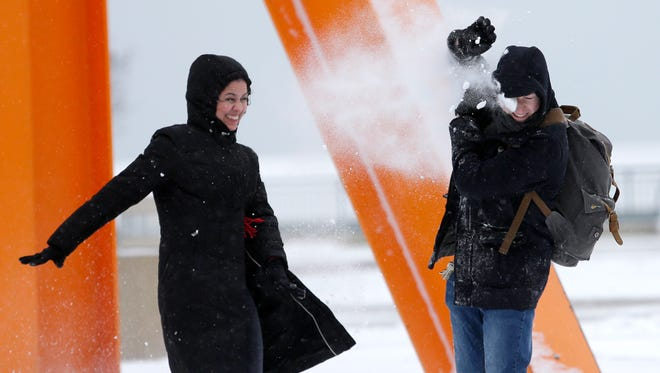 Deise Costa, throws a snowball at her husband Tim Crowley, along W. Wisconsin Ave. near the Milwaukee Art Museum in Milwaukee on Sunday. The couple were visiting from Chicago and enjoying the recent snowfall.