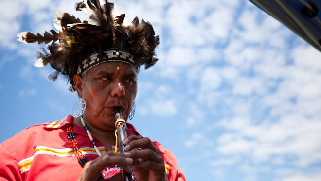 Bill Crouse from Salamanca, NY tests out a Native American flute during Ganondagan's Dance and Music Festival in Victor on Saturday, July 26, 2014.