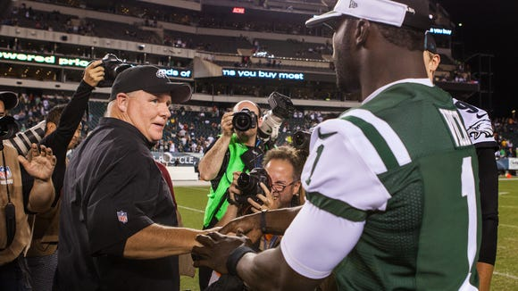 Eagles head coach Chip Kelly talks with former Eagles quarterback Michael Vick after a preseason football game at Lincoln Financial Field on Thursday night, August 28, 2014.