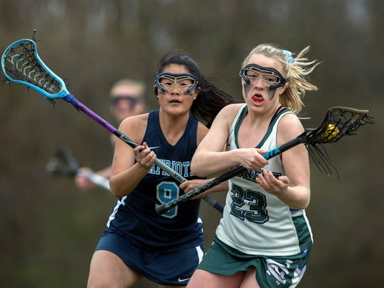 Colts Neck's Katie Thomas tries to stay one step ahead of Freehold Township's Katie Peterson during first half action. Freehold Township Girls Lacrosse vs Colts Neck in Colts Neck, NJ on April 24, 2018.