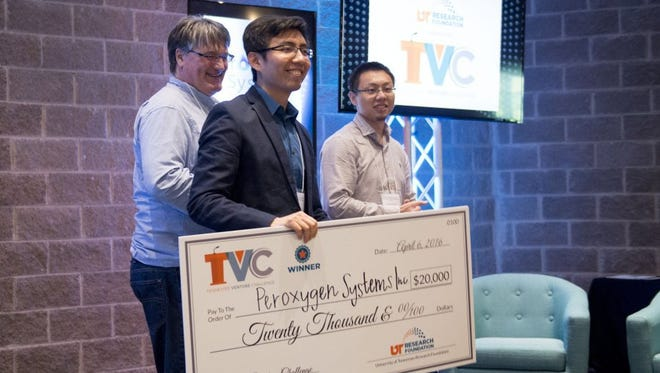 Ming Qi, center, and his partners, Tom Zawodzinski, left, and Menqi Zhang, celebrate after their startup, Peroxygen Systems Inc., won the $20,000 grand prize in the final round of the Tennessee Venture Challenge at The Foundry on April 6, 2016.