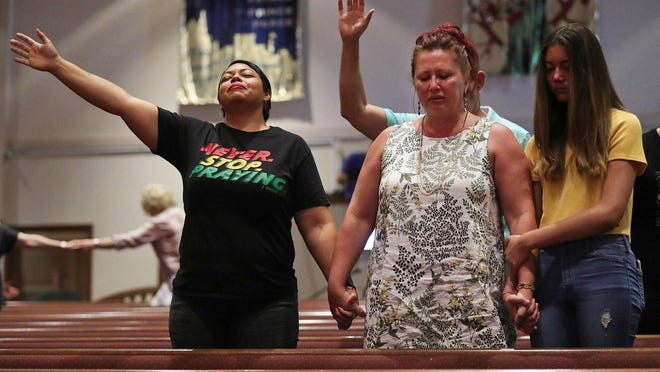 Rachel Socorro-Graces, a minster at Revived Ministries, left, prays with Jinka Bloom of Uniontown, center, following a sermon condemning racism at Community Vineyard Church, Sunday, June 7, 2020, in Cuyahoga Falls, Ohio.