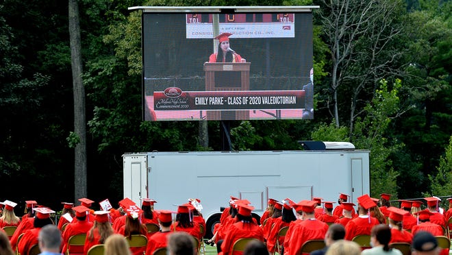 Valedictorian Emily Parke is projected on a large television screen as she speaks at last year's outdoor graduation at Milford High School.