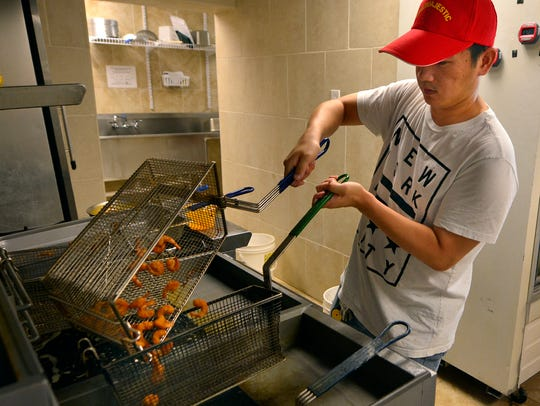Owner Guang Li makes a batch of fried shrimp at the