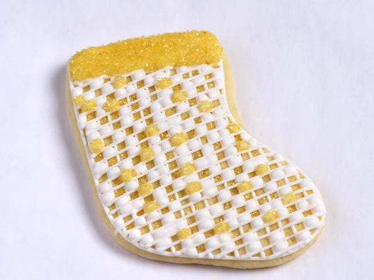 A stocking cookie from Tot's Treats is first contoured in icing to define the limits of the decorated area.