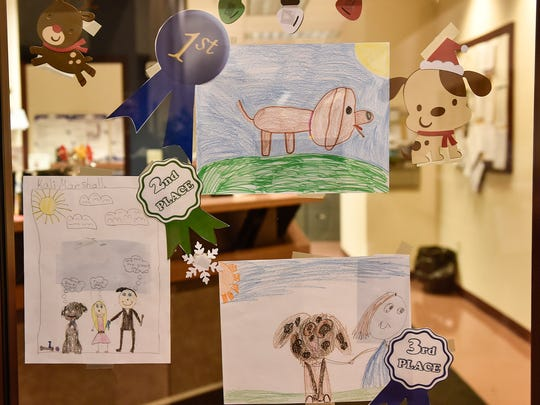The first-, second-, and third-place winners' drawings of their dogs are on display in the window of the Marion County Auditor's office.