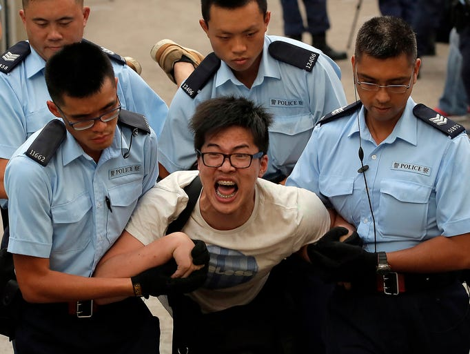 A protester is removed by police officers after an overnight sit-in on July 2 on Chater Road in Hong Kong. Police arrested 511 people who refused to leave a street in the city's financial district, a day after thousands of protesters staged a march against China's interference in local elections.
