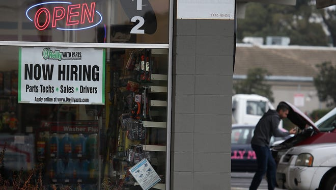A now hiring sign is posted in window of an O' Reilly auto parts store on Nov. 7, 2014 in San Rafael, Calif.