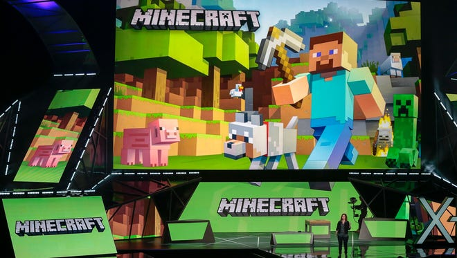 """Lydia Winters, at podium, shows off Microsoft's """"Minecraft"""" built specifically for HoloLens during a live demo at the Xbox E3 2015 briefing ahead of the Electronic Entertainment Expo at the University of Southern California's Galen Center on Monday, June 15, 2015 in Los Angeles. Microsoft is promoting the next installment in its popular sci-fi franchise, """"Halo 5: Guardians,"""" at the Electronic Entertainment Expo."""