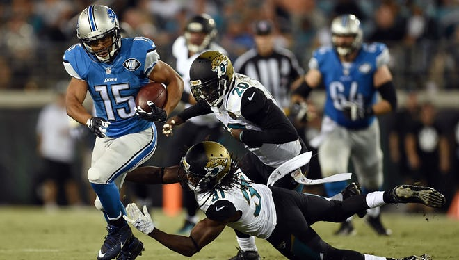 JACKSONVILLE, FL - AUGUST 28:  Golden Tate #15 of the Detroit Lions avoids a tackle by Davon House #31 of the Jacksonville Jaguars during the first quarter of a preseason game at EverBank Field on August 28, 2015 in Jacksonville, Florida.